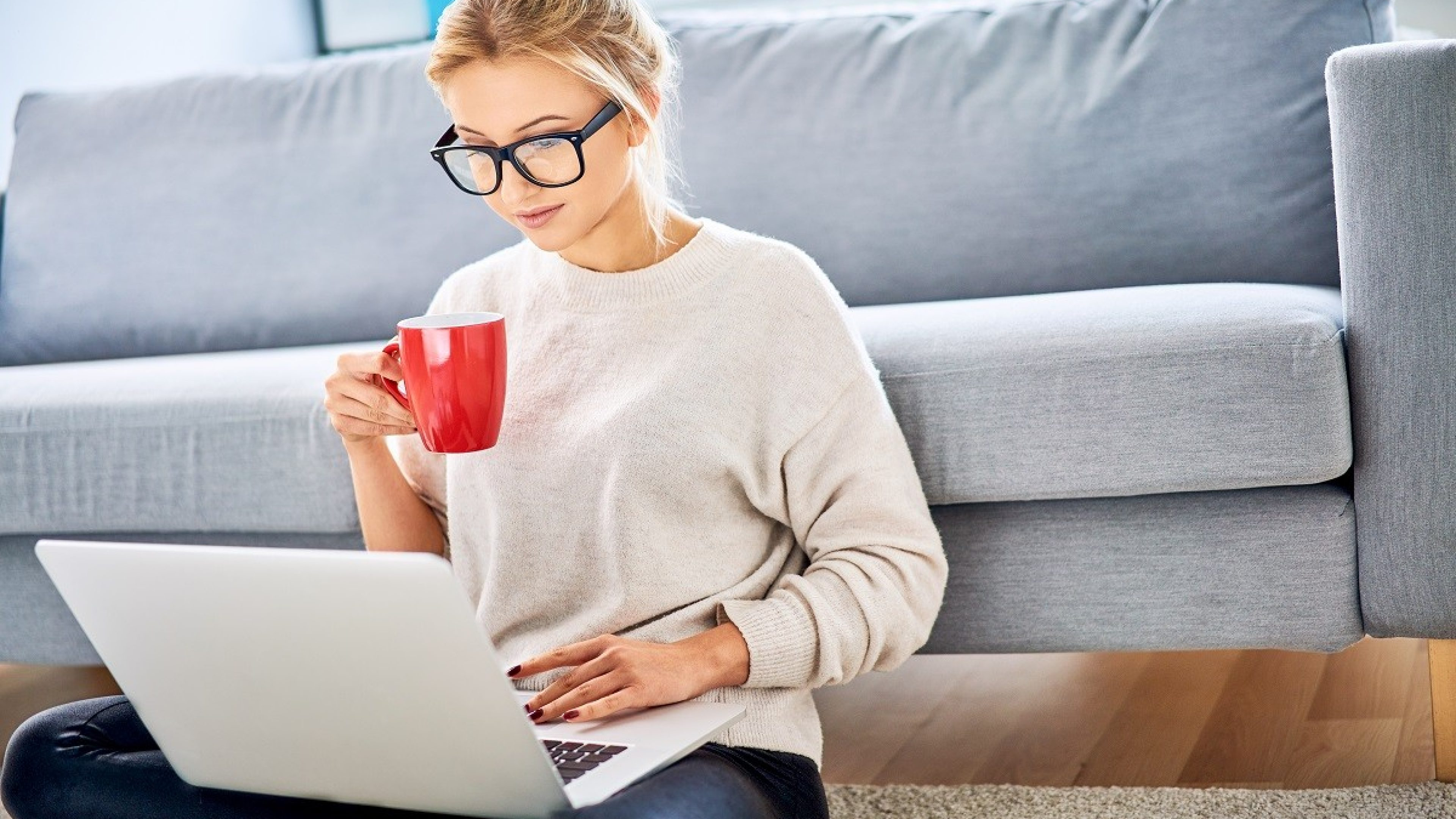 Young woman having coffee while using laptop and sitting on floor at home